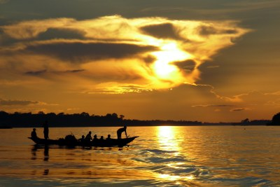 A traditional wooden boat floats on the Congo River of the Democratic Republic of the Congo.