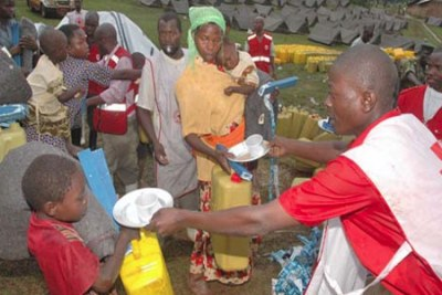 A young boy receives relief items from workers of the Uganda Red Cross society.