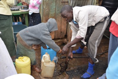 Residents of Kibera in Nairobi pump water.