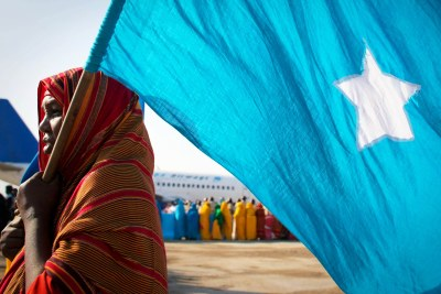 Woman carries the Somali flag.
