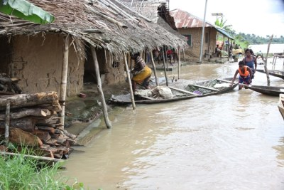 Women with a dug-out canoe in front of their flooded homes in Toru-Orua in Sagbama.