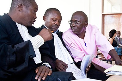 Leo Mugesera, far right, speaking to his lawyers in court.