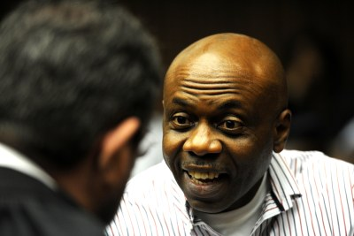 Nigerian Henry Okah, found guilty of masterminding two car bomb blasts in Abuja, Nigeria, speaks to his legal representative at the High Court in Johannesburg, South Africa. (file photo)