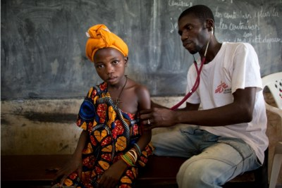 MSF nurse Eric Konate examines a sick child suffering from malaria at a mobile clinic in Bolom Village, Central African Republic.