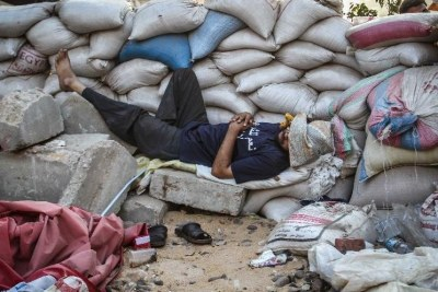 A supporter of Egypt's ousted President Mohammed Morsi sleeps by sand barriers set up by protesters around Raba'a square in Cairo (file photo).