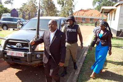 Under watch. King Mumbere escorted by a police officer on arrival at the Jinja Chief Magistrate's Court.