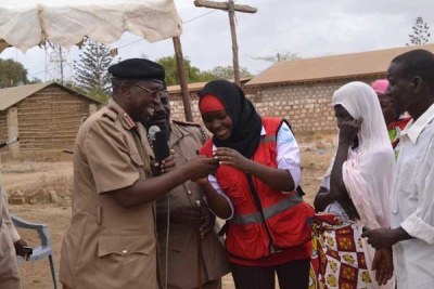 Kilifi County Commissioner Joseph Keter (left) and county Kenya Red Cross manager Hakima Masoud (right) verify an SMS text from one of the beneficiaries of the cash transfer programme launched in Kaloleni.