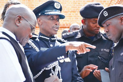 IGP Kale Kayihura chats with some police officers at Lubaga cathedral recently