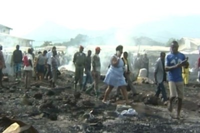 People assess the damage in part of a burned down market in Limbe