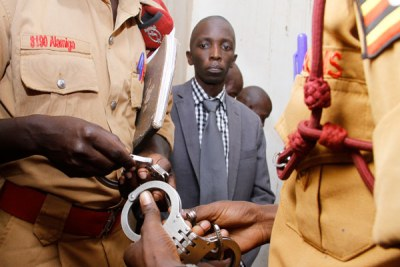 Brian Bagyenda (middle) looks on as Prison wardens prepare to handcuff him.