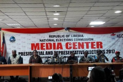 Chairman of the National Elections Commission Jerome G. Korkoya, fourth from left, announces results.