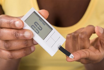 A woman testing for blood sugar level.