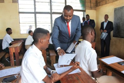 State Minister for Primary and Secondary Education, Isaac Munyakazi, distributes examination papers at GS Remera examination centre in Kigali Tuesday morning.