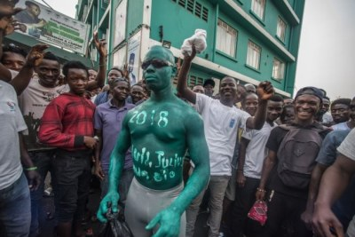 A supporter of Julius Maada Bio and the Sierra Leone People's Party wears green paint, the party's color, outside of SLPP headquarters in Freetown, Sierra Leone.