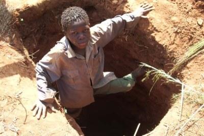 Photo Archive - Sidio Elias, 12 ans, sort du puits de mine qu'il a creusé avec deux autres enfants.