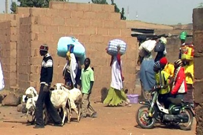 Residents in the the Nasarawa Gown area of Jos in Plateau State flee for safety.