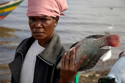 A woman displays fish in lake Victoria,Kenya.