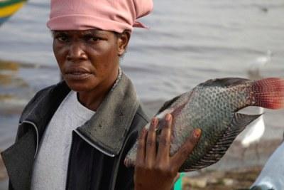 Une femme exhibe un poisson du lac Victoria au Kenya 2008