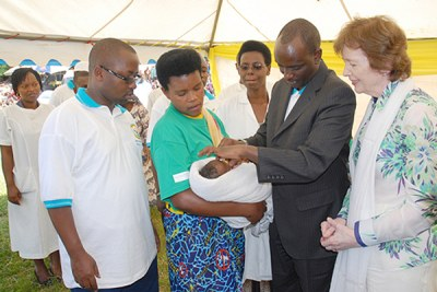 The Minister of Health, Dr. Richard Sezibera (2nd right) administers a Polio Vaccine to a Child as GAVI Chairperson Mary Robinson (right) looks on.