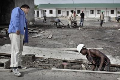 Un ouvrier zambien effectue des travaux de construction à la China Luanshya Mine sous le regard d'un directeur chinois.