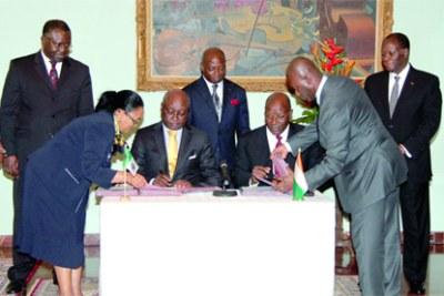 Retour de la Bad : UN NOUVEL ACCORD DE SIEGE SIGNE - Signature des documents sous le regard du Président Ouattara (debout à l'extrême droite).