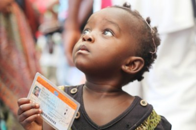 Little girl with a voting card.