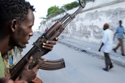 Un soldat de l'Armée nationale somalienne parcourt les rues de Mogadiscio, en Somalie, à l'arrière d'un technicien.