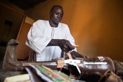 Sheji Aldine Abdala, membre d'une association soudanaise assistant les personnes handicapées répare une jambe prothétique.