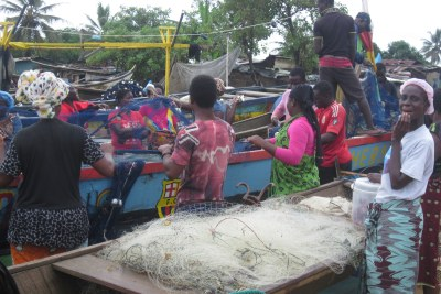 Market women help fishermen prepare their nets for the night time fishing expedition (file photo).