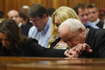 Paralympian Oscar Pistorius's father Henke Pistorius kisses the hand of his daughter Aimee Pistorius while judgment is handed down at the High Court in Pretoria (file photo).