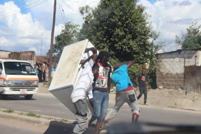 De jeunes zambiens transportant un congélateur lors des scènes de pillage.