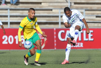 Seturumane Tsepo of Lesotho takes a shot at goal while challenged by Rivaldo Coetzee of South Africa during the 2016 Cosafa Cup Quarterfinals match