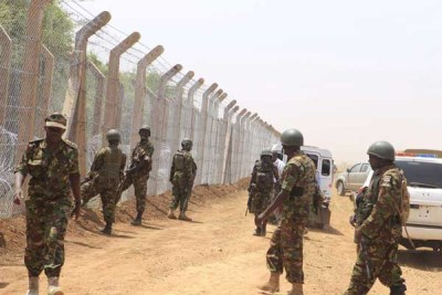 Kenyan soldiers on guard as the erection of a security fence along the Kenya-Somalia border goes on.