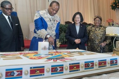 King Mswati III in his suit of diamonds and wearing his U.S.$1.6 million watch cuts his birthday cake (file photo).