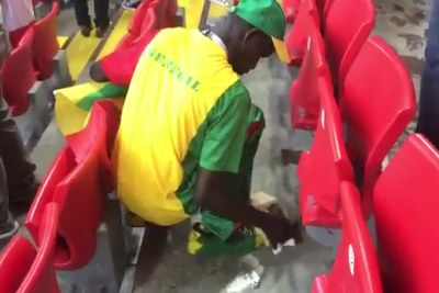 A Senegalese fan picking up papers.