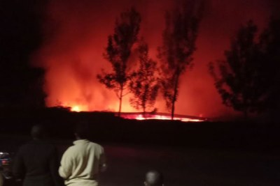 Kisii residents watch as fire consumes a dormitory at Kisii High School on July 10, 2018.