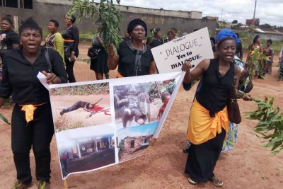 Women protest, holding up a poster with images of atrocities committed in an ongoing conflict between government forces and armed separatists, in Bamenda, Cameroon, Sept. 7, 2018.