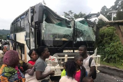 A bus attacked by armed separatist and its passengers are seen at Akum, a village 10 Kilometers from Bamenda, the capital of the Cameroon's English speaking northwest region, Sept. 9, 2018.