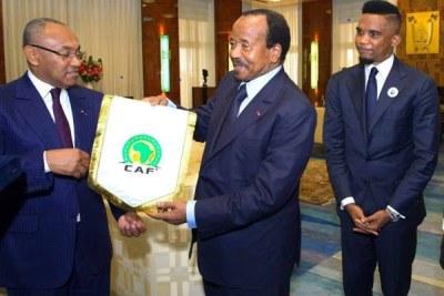Le 2 octobre 2018, le président camerounais Paul Biya (au centre) reçoit un cadeau du président des CAF, à la Maison de l'État à Yaoundé, en présence de la légende du football camerounais, Samuel Eto'o.