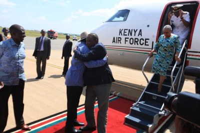 Raila Odinga receives President Kenyatta at the Kisumu International Airport on December 13, 2018.