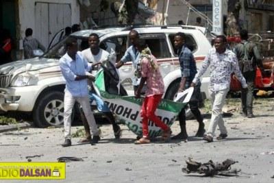 Civilians carry the dead body of a man killed in a car bomb explosion near a hotel in Mogadishu, Somalia, March 28, 2019 (file photo).