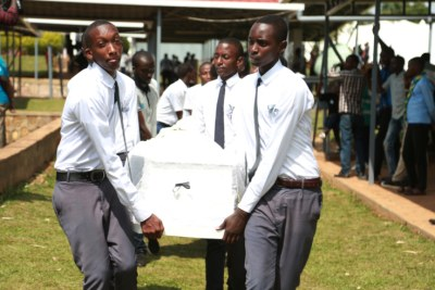 Youths carry a coffin containing remains of the victims of genocide (file photo).