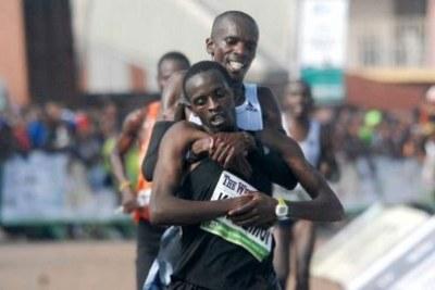 Simon Cheprot helps countryman Kenneth Kipkemoi to the finish line during the Okpekpe International 10km Road Race.