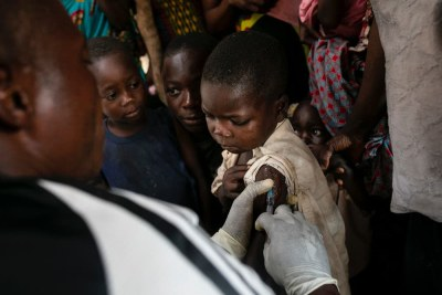 An MSF nurse vaccinates a young boy against measles during the vaccination campaign in Kweba village, Lungonzo district, DRC, May 2019.