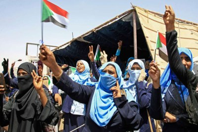 Sudanese women wave flags during outside army headquarters in Khartoum (file photo).