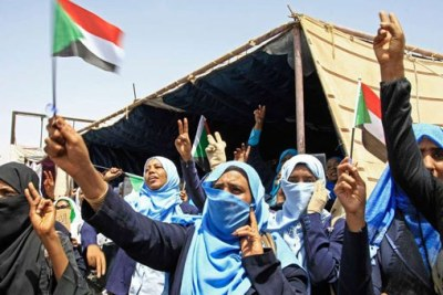 Sudanese women wave flags during outside army headquarters in Khartoum.