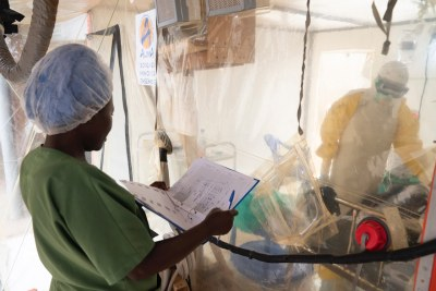 Health workers talk to an Ebola patient, while a nurse consults a chart outside at an Ebola treatment centre in Beni, Democratic Republic of the Congo.