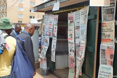 Camerounais lisant des journaux dans la rue.