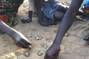 Three girls play the game isolo on the ground in the lead-affected township of Waya in Kabwe. Soil is the main source of lead exposure in Kabwe.