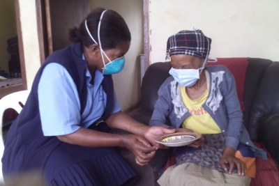 A community care worker providing care to a patient at her home (file photo).